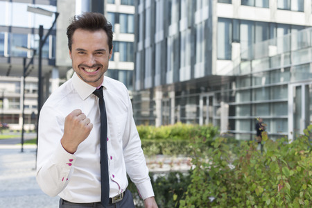 clenching teeth: Portrait of cheerful businessman with clenched fist standing outside office building