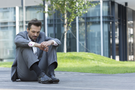 hugging knees: Full length of sad businessman sitting on path outside office