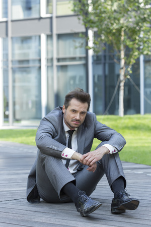 hugging knees: Full length portrait of stressed businessman sitting on path outside office LANG_EVOIMAGES