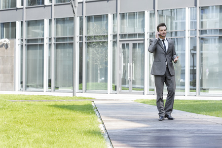 walking paths: Businessman using cell phone while walking on path outside office LANG_EVOIMAGES