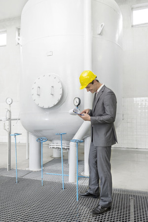 storage tank: Full length side view of young male supervisor with clipboard standing by storage tank in industry