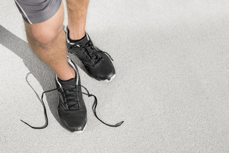 untied: Low section of sporty man with untied shoelace standing on street LANG_EVOIMAGES