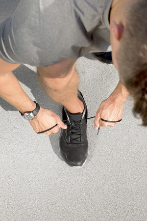High angle view of sporty man tying shoelace on street Stock Photo