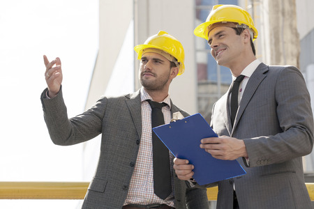 construction site helmet: Young male architects with clipboard discussing at construction site