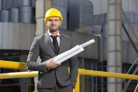 architect: Portrait of confident young architect holding blueprints outside industry LANG_EVOIMAGES