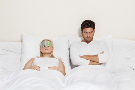 Displeased young man with woman sleeping in bed Stock Photo