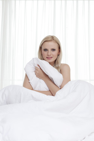bedsheet: Portrait of beautiful young woman holding bedsheet in bed