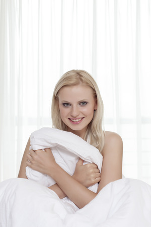 bedsheet: Portrait of attractive young woman holding bedsheet in bed