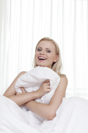 bedsheet: Portrait of cheerful young woman covering herself with bedsheet in bed