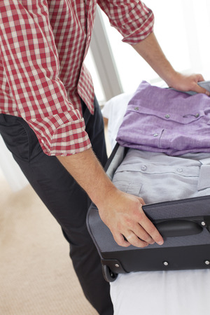 Midsection of young man unpacking suitcase in hotel room Stock Photo