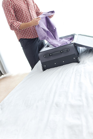 midsection: Midsection of young businessman unpacking suitcase in hotel room