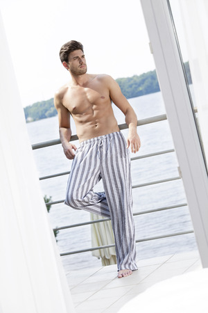 partially nude: Full length of handsome young man leaning on hotel balcony looking away LANG_EVOIMAGES