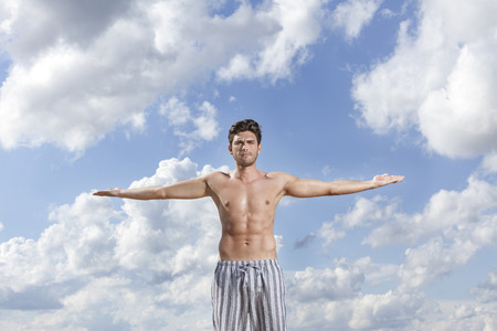 partially nude: Muscular young man standing with arms wide open against cloudy sky