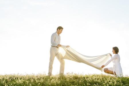 picnic blanket: Vista lateral de la mujer y el hombre difusi�n manta de picnic en la hierba durante d�a soleado
