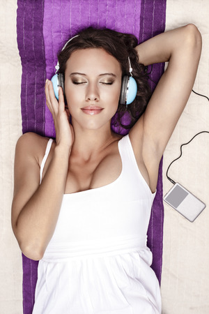 portable mp3 player: Young woman listening to music through MP3 player using headphones while lying on picnic blanket