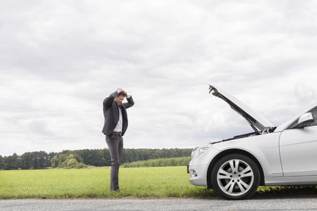 Sad young businessman standing with hands on head near broken car at countryside Stock Photo