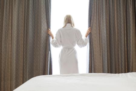 opening window: Vista posterior de la mujer joven en albornoz cortinas de la ventana de apertura en la habitaci�n del hotel