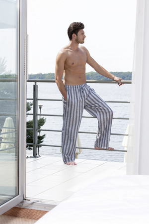 partially nude: Full length of shirtless young man on hotel balcony looking away