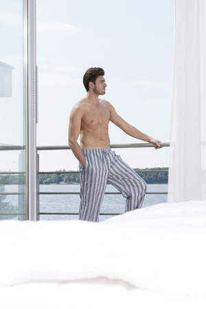 partially nude: Shirtless young man on hotel balcony looking away LANG_EVOIMAGES