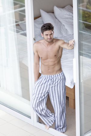 partially nude: Full length of shirtless young man standing at balcony doorway LANG_EVOIMAGES