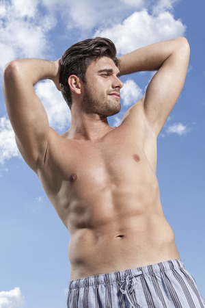 partially nude: Shirtless young man with hands behind head against cloudy sky