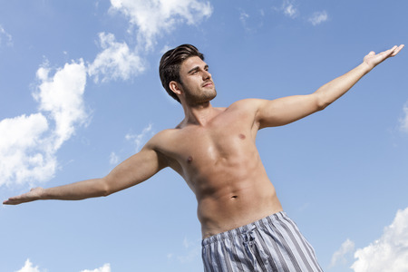 partially nude: Muscular young man standing arms outstretched against cloudy sky