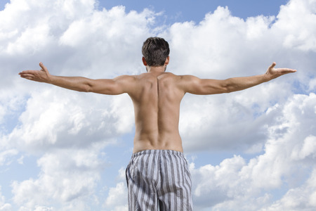 partially nude: Rear view of shirtless young man standing arms outstretched against cloudy sky