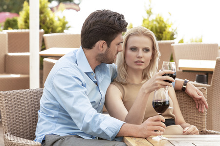 couple talking: Young couple talking while having red wine at outdoor restaurant