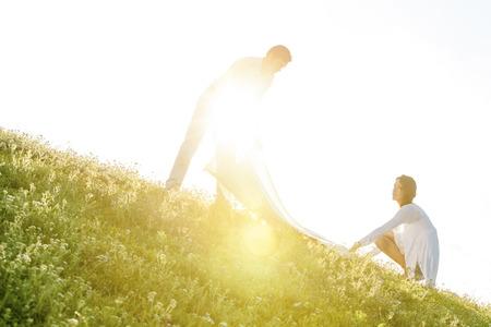 picnic blanket: Inclinaci�n de la imagen de la joven pareja difusi�n manta de picnic en la hierba durante d�a soleado LANG_EVOIMAGES