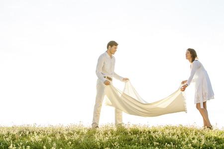 picnic blanket: Pareja joven que se separa manta de picnic en el c�sped durante el d�a soleado LANG_EVOIMAGES