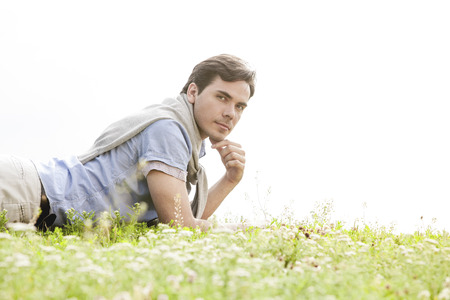 ���clear sky���: Portrait of young man lying on grass against clear sky