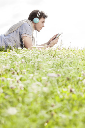 portable mp3 player: Side view of man listening to music on MP3 player using headphones while lying in park against clear sky