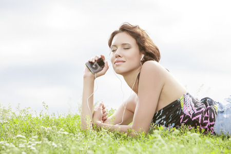 portable mp3 player: Side view of woman listening to music through MP3 player using headphones while lying on grass against sky LANG_EVOIMAGES