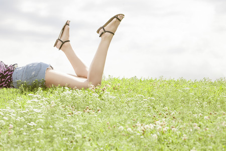 low section: Low section of woman lying on grass against sky LANG_EVOIMAGES