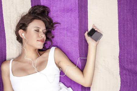 picnic blanket: Mujer Relaxed que escucha la m�sica a trav�s de reproductor de MP3 con auriculares mientras est� acostado en una manta de picnic
