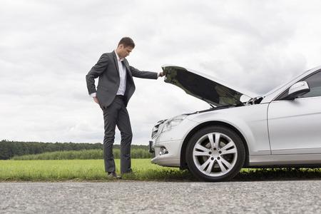 田舎で車のエンジンを分解検査青年実業家の全長サイドビュー