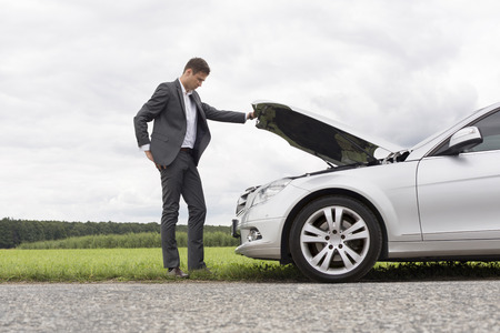 Full length side view of young businessman examining broken down car engine at countryside