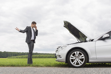 田舎で壊れた車で携帯電話を使用して不満の青年実業家