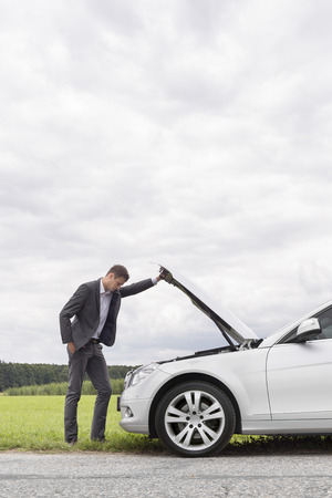 broken car: Side view of young businessman examining broken down car engine at countryside