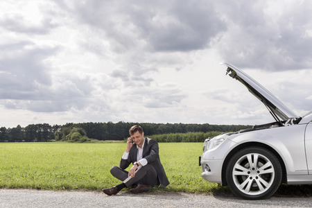broken: Full length of unhappy young businessman using cell phone by broken down car at countryside