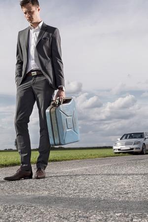 petrol can: Longitud total de joven empresario triste llevar bid�n de gasolina con el coche roto en fondo en la campi�a LANG_EVOIMAGES