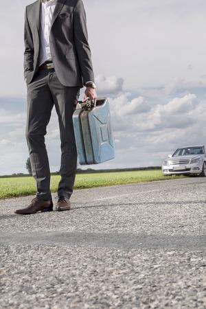 petrol can: Secci�n baja de hombre de negocios joven que lleva la lata de gasolina con el coche roto en el fondo en el campo