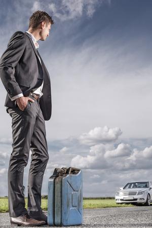 petrol can: Longitud total de joven empresario con gasolina puede mirar coche roto en el campo