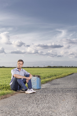 petrol can: Full length of young man with empty petrol can sitting by country road