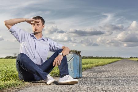petrol can: Longitud total de joven ojos blindaje mientras estaba sentado con lata de gasolina en la carretera nacional