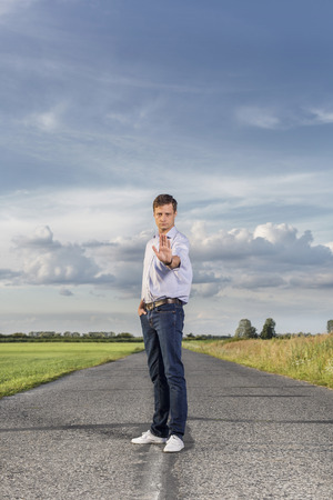 stop gesture: Portrait of serious young man making stop gesture at country road LANG_EVOIMAGES