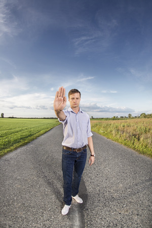 stop gesture: Full length portrait of young man making stop gesture at country road