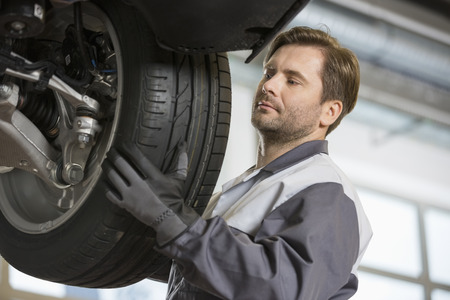 tire repair shop: Mid adult technician adjusting cars tire in workshop