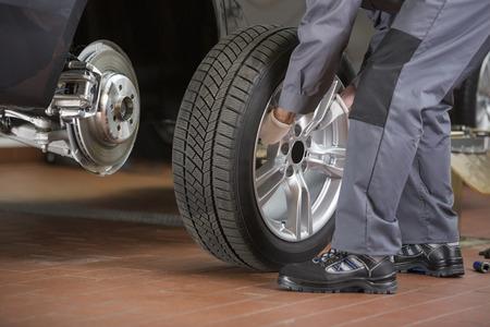 tire repair shop: Low section of repairman fixing cars tire in repair shop LANG_EVOIMAGES