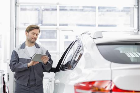 mecanico: Hombre trabajador de reparaci�n utilizando tablet PC mientras est� de pie en coche en el taller LANG_EVOIMAGES